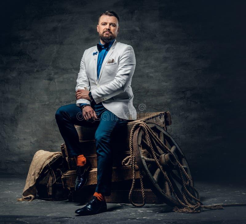 El varón barbudo vestido en vaqueros, una chaqueta blanca y una corbata de lazo sienta o imagen de archivo libre de regalías