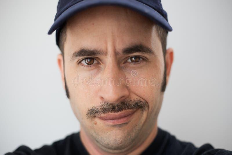 El varón blanco con un bigote prominente y un sombrero contra un fondo inconsútil mira la cámara fotografía de archivo libre de regalías
