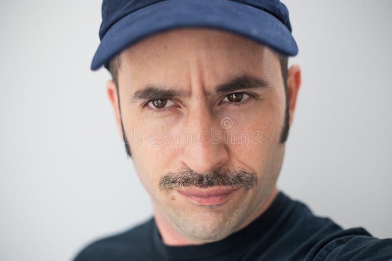 El varón blanco con un bigote prominente y un sombrero contra un fondo inconsútil mira la cámara foto de archivo