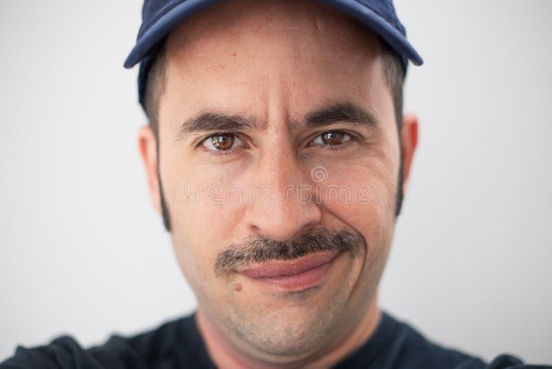 El varón blanco con un bigote prominente y un sombrero contra un fondo inconsútil mira la cámara imagen de archivo