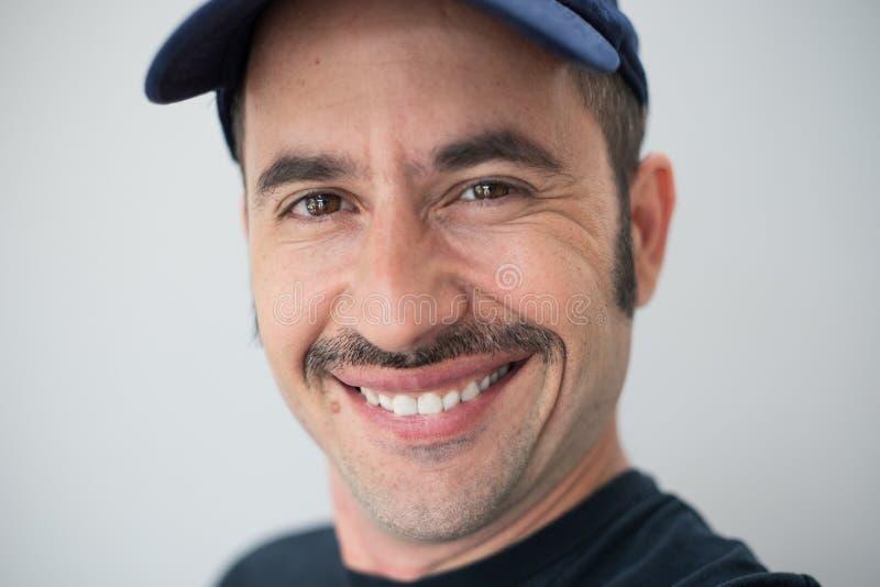 El varón blanco con un bigote prominente y un sombrero contra un fondo inconsútil mira la cámara y las sonrisas imagen de archivo