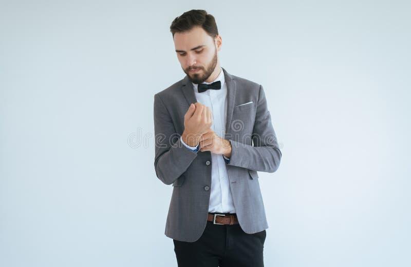 El varón caucásico hermoso con la barba en la situación formal del smoking y del traje y vestido para arriba en el fondo blanco,  imágenes de archivo libres de regalías