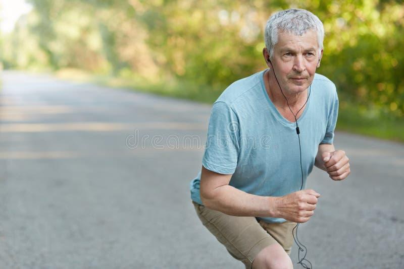 El varón confiado jubilado se coloca en el comienzo, listo para participar en comeptitions del deporte, escucha música con los au imagenes de archivo