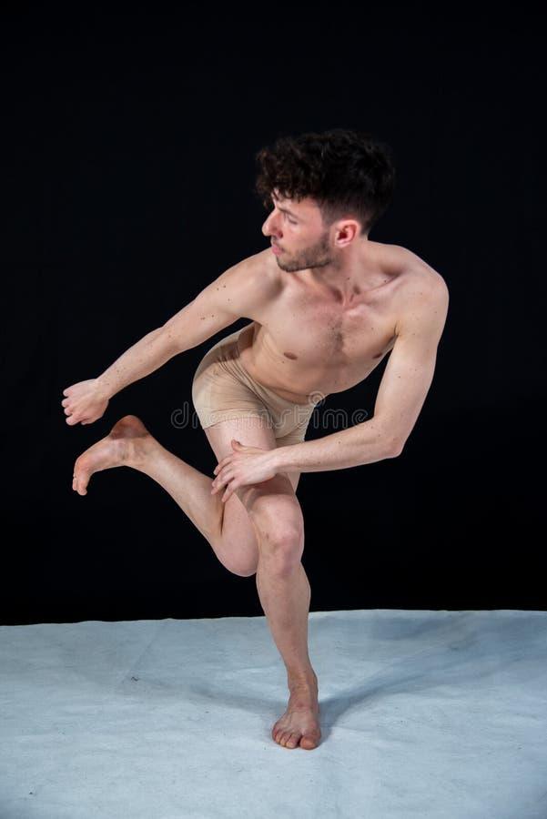 El varón cuerpo-coloreó al bailarín de ballet que practicaba en el estudio con las manos y las piernas en un fondo negro foto de archivo libre de regalías