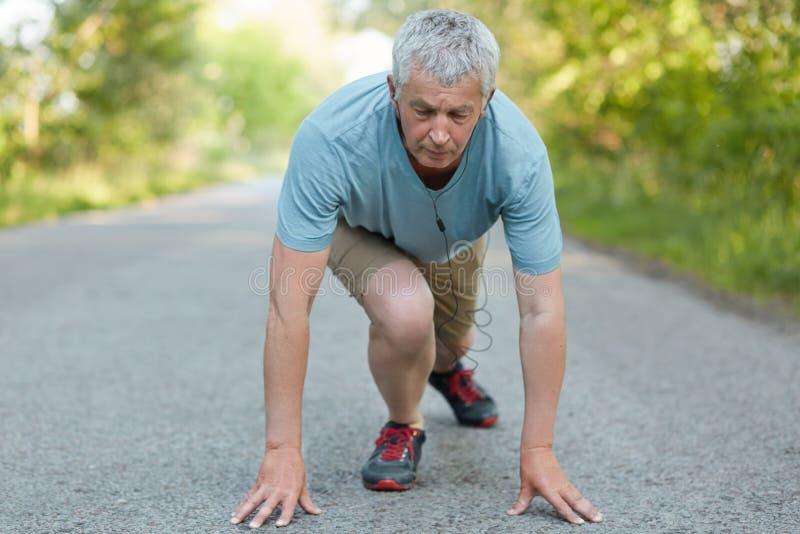 El varón elederly fuerte determinado participa en los maratones, listos para correr, vestidos en ropa de deportes, las ayudas for foto de archivo libre de regalías