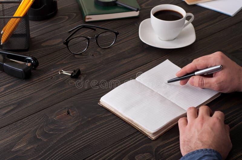 El varón escribe en un diario en la mesa de la oficina imagenes de archivo