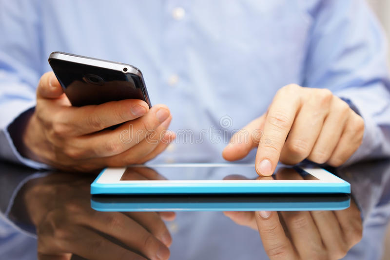 El varón está utilizando el teléfono móvil y la tableta elegantes en lo mismo fotografía de archivo libre de regalías