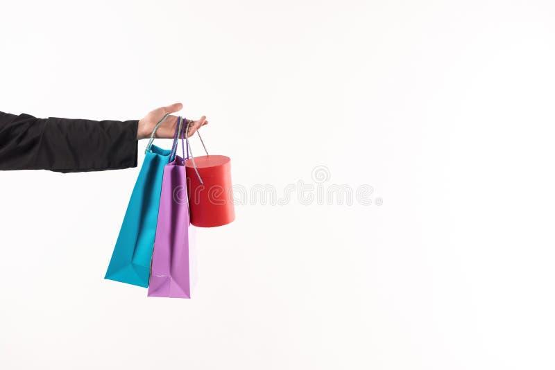 El varón estiró la mano sostiene las bolsas de papel imágenes de archivo libres de regalías