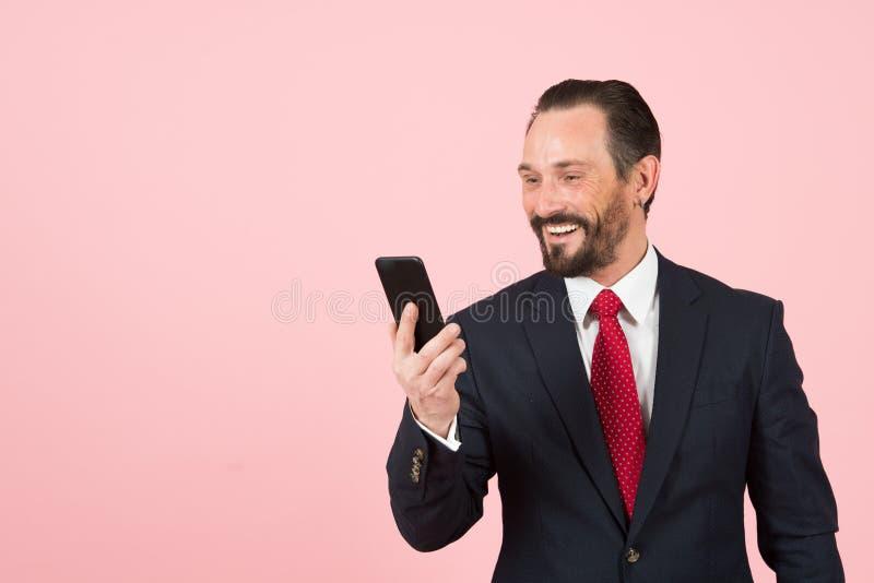 El varón feliz barbudo en traje y lazo rojo mira smartphone en fondo rosado El hombre de negocios hace la charla video con los cl imagen de archivo