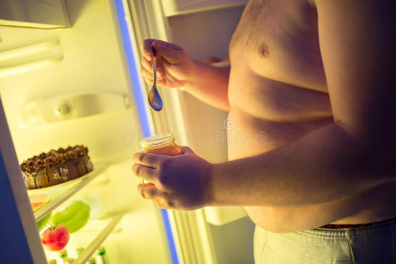 El varón gordo come en el atasco de la noche del tarro con la cuchara grande foto de archivo
