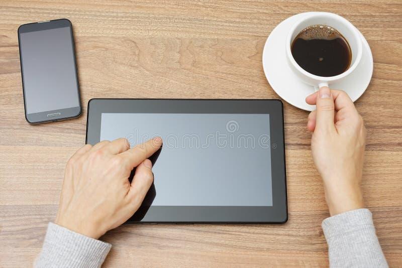 El varón joven está utilizando la PC de la tableta y el café de consumición foto de archivo
