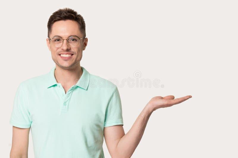 El varón joven feliz en vidrios señala en el espacio libre a un lado fotografía de archivo