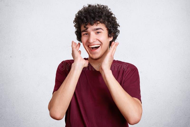 El varón joven rizado alegre que está en el buen humor, risas feliz como oye broma agradable, sonríe, presenta contra el muro de  fotos de archivo libres de regalías