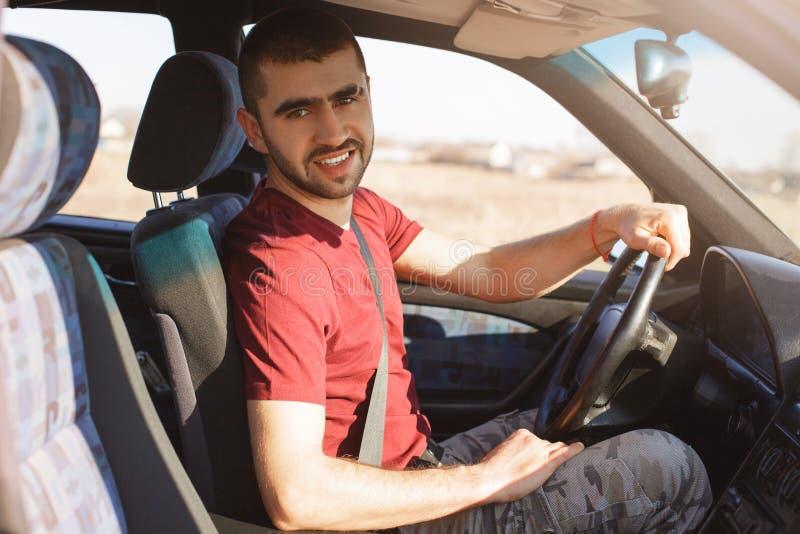 El varón joven sin afeitar hermoso con rastrojo se sienta en coche, tiene rotura después de conducir, mira la cámara, disfruta de fotografía de archivo libre de regalías