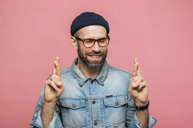 El varón sin afeitar positivo con mirada alegre cruza los fingeres, guarda el ojo fotografía de archivo