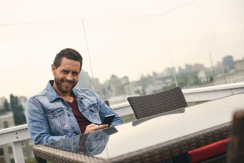 El varón sonriente se está sentando en la tabla en café foto de archivo libre de regalías