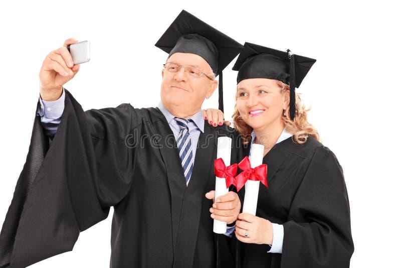 El varón y la hembra maduros en la graduación viste tomar un selfie imagenes de archivo