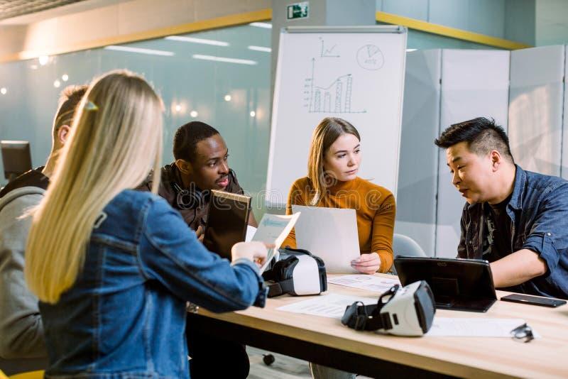 El varón y los arquitectos o los freelancers de sexo femenino trabajan con las tabletas y los ordenadores portátiles, auriculares imagen de archivo
