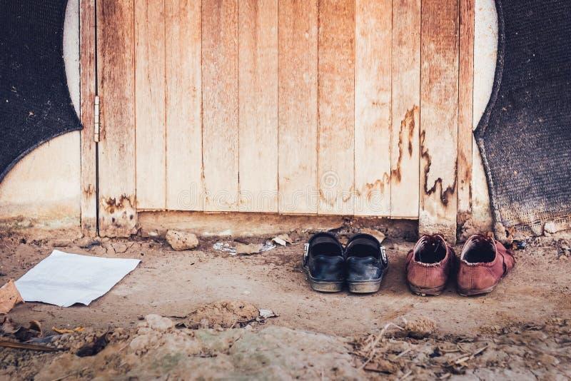 El varón y los estudiantes sacan sus zapatos en la entrada delantera de una cabaña abandonada foto de archivo