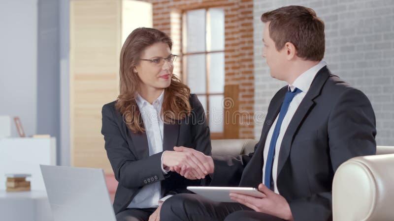 El varón y los socios comerciales femeninos llegan al acuerdo acertado, sacudiendo las manos imagen de archivo