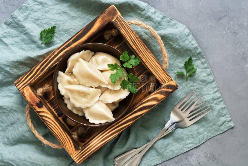 El vareniki ruso de la comida con las patatas se sirve en un cuenco en una caja de madera Fondo gris, endecha plana imágenes de archivo libres de regalías
