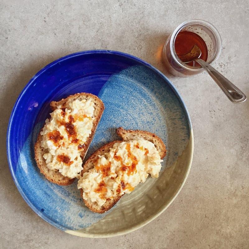 El vegano rompió la ensalada del garbanzo en tostada del pan amargo con llovizna del harissa imagenes de archivo
