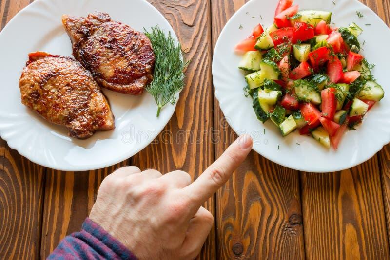 El vegetariano elige la ensalada en vez de la carne frita imagenes de archivo