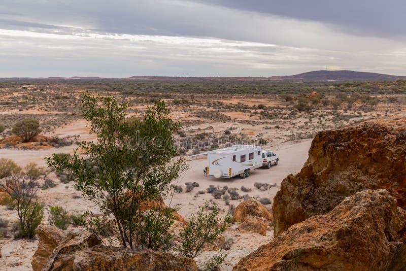 El vehículo del tracción cuatro ruedas y la caravana blanca grande acamparon al lado de un afloramiento rocoso foto de archivo