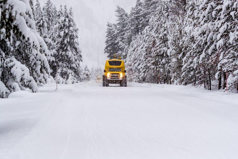El vehículo resistente del autobús de la nieve ara sobre la nieve de la carretera 20 en Yellowstone en invierno fotos de archivo