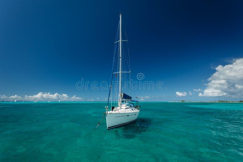 El velero blanco amarró en aguas tropicales hermosas del océano de la turquesa en British Virgin Islands foto de archivo