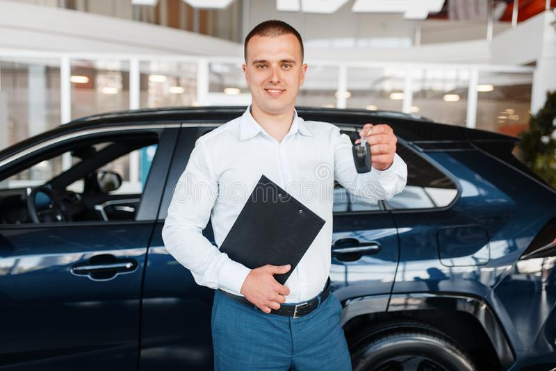 El vendedor da dominante al nuevo coche en la sala de exposición foto de archivo