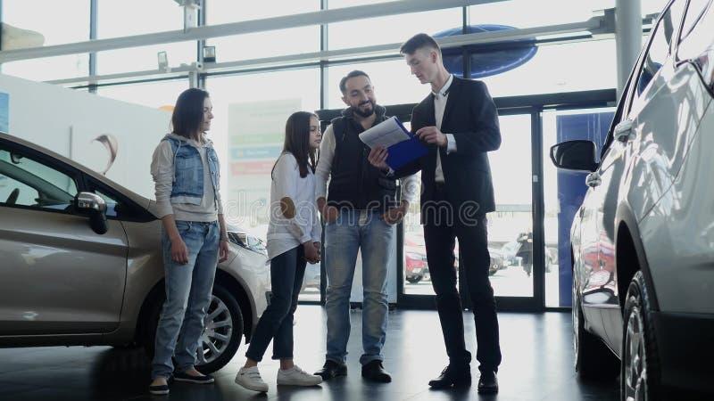 El vendedor de coches muestra una información joven de la familia sobre su nuevo coche foto de archivo libre de regalías