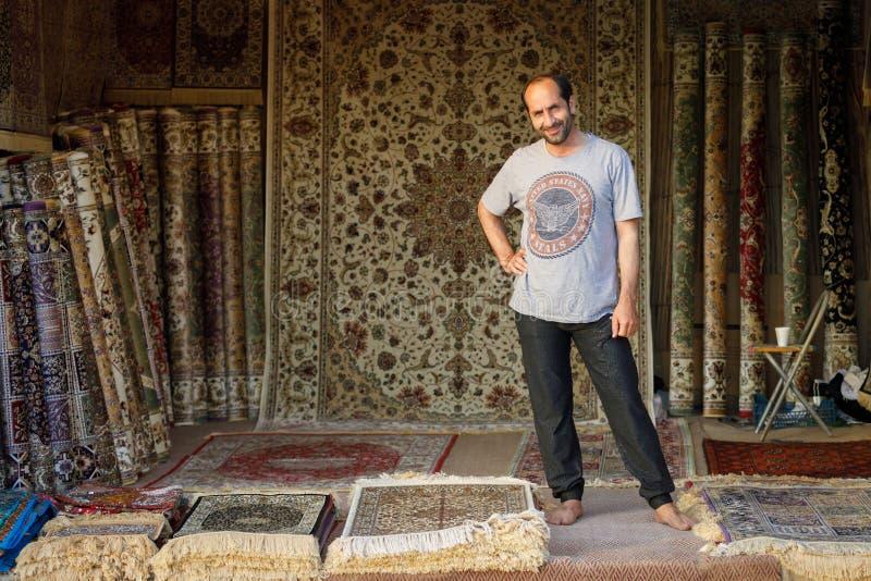 El vendedor de la alfombra acoge con satisfacción a compradores en su pequeña tienda durante viaje del safari del desierto fotografía de archivo libre de regalías