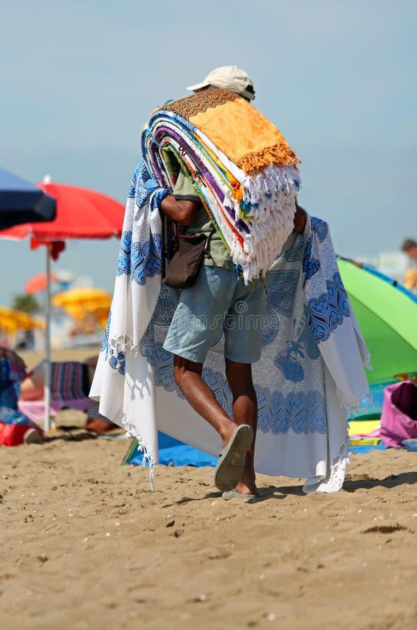 el vendedor de la alfombra de la calle camina en la playa soleada fotografía de archivo libre de regalías