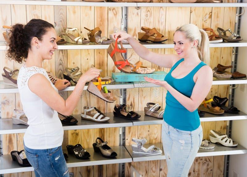 El vendedor de la muchacha ayuda a la muchacha rubia con una selección de zapatos del verano imagenes de archivo