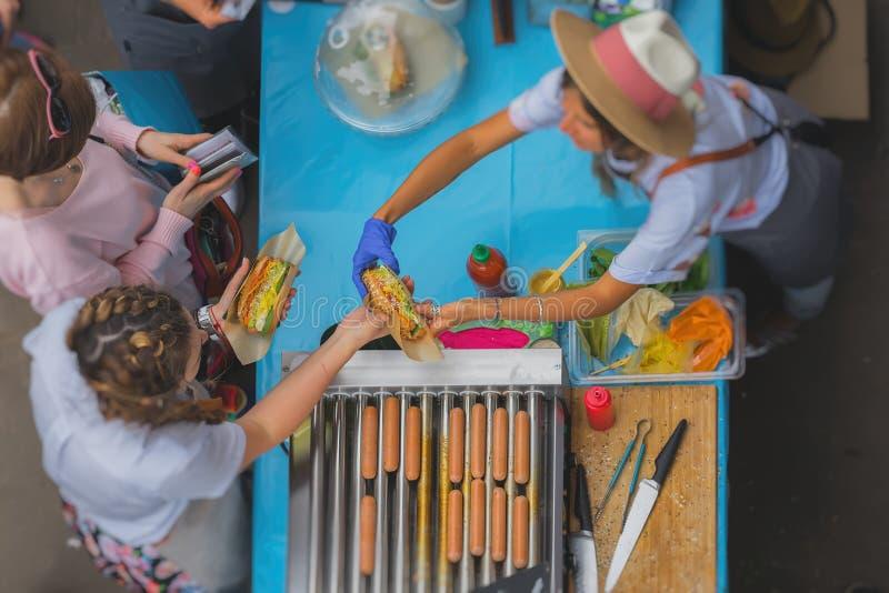 El vendedor de la muchacha sirve a clientes Venta y servicio con la comida sana de la calle del vegano, foco selectivo Visión sup foto de archivo