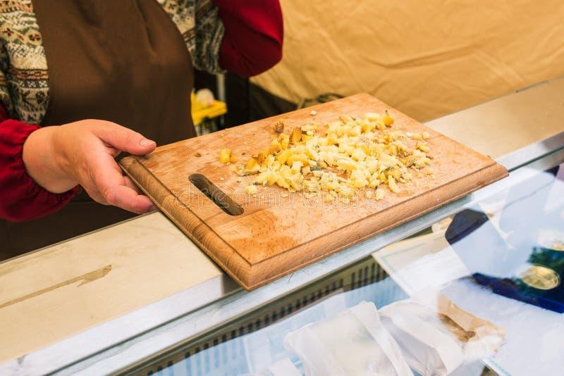 El vendedor de la mujer conduce probar el queso Un productor del granjero presenta y vende su queso Tajadera con queso Productos  imagenes de archivo