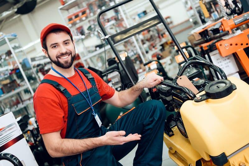 El vendedor está presentando con el compresor de la placa en primero plano en tienda de las herramientas eléctricas fotografía de archivo libre de regalías