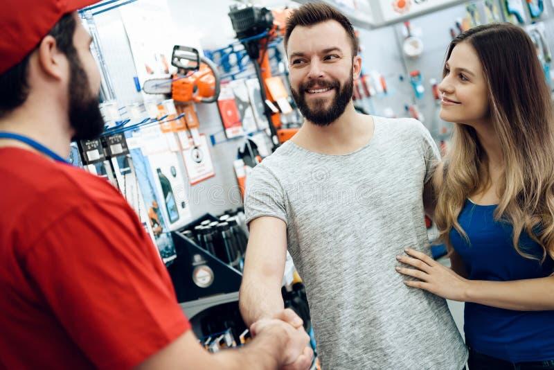 El vendedor está sacudiendo las manos con el cliente barbudo en tienda de las herramientas eléctricas foto de archivo libre de regalías