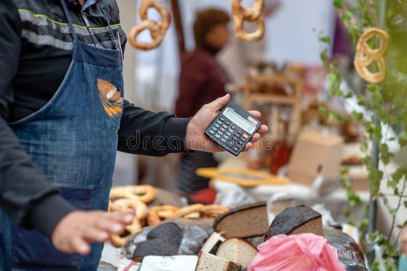 El vendedor expresa el precio del producto calculado por el calc imagen de archivo libre de regalías