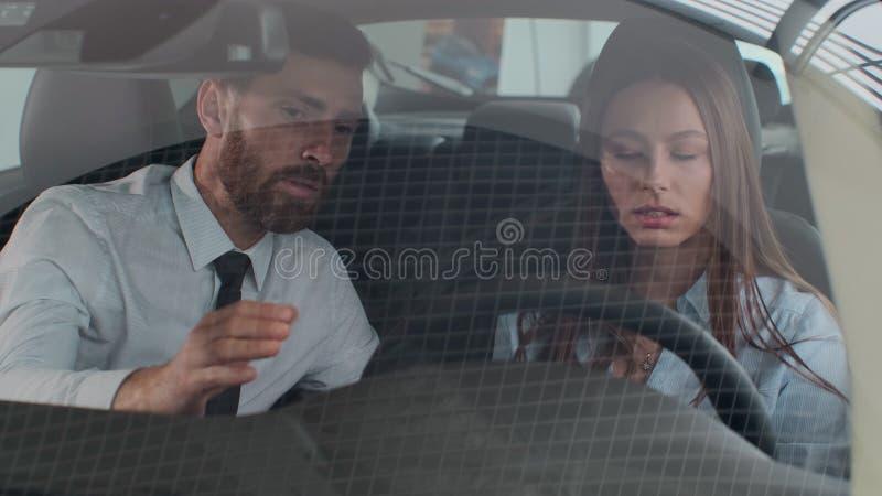 El vendedor muestra las características del coche para el cliente El coche es nuevo El vendedor hace el mejor para vender éste fotos de archivo