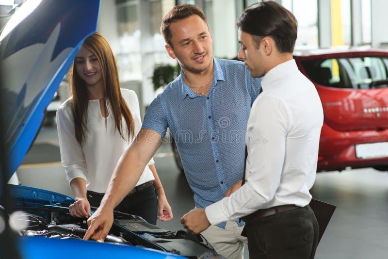 El vendedor muestra el motor de coche imagenes de archivo