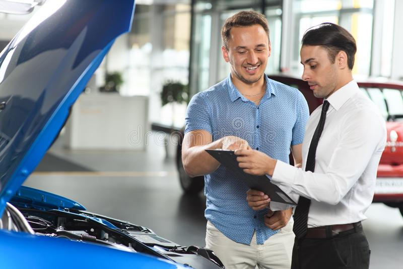 El vendedor muestra el motor de coche para su cliente fotografía de archivo
