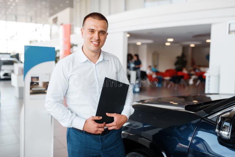 El vendedor muestra el nuevo coche en la sala de exposición fotos de archivo libres de regalías