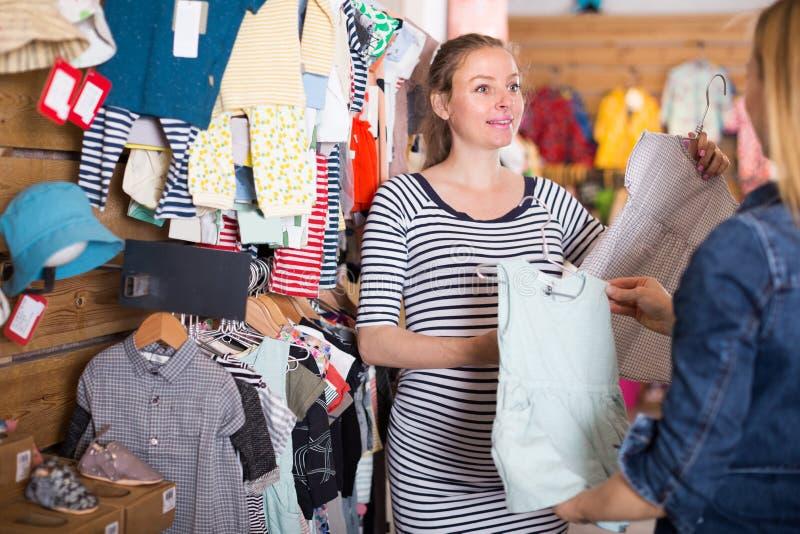 El vendedor ofrece el vestido del bebé de la mujer embarazada en sto de la ropa de los niños foto de archivo
