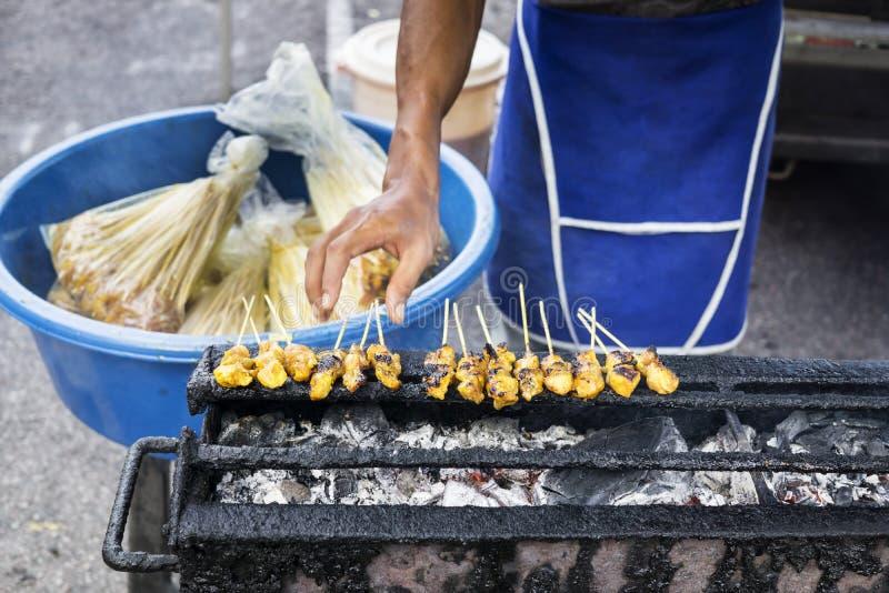 El vendedor satay que viajaba asó a la parrilla satay en el mercado de la noche imágenes de archivo libres de regalías