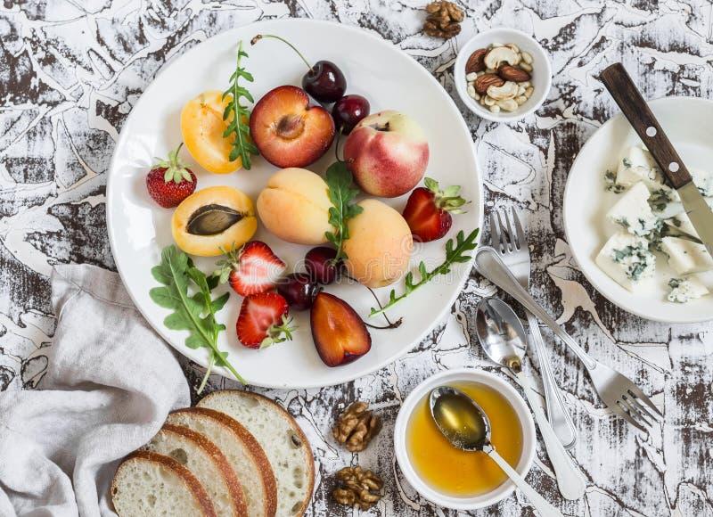 El verano da fruto - los albaricoques, los melocotones, los ciruelos, las cerezas, las fresas y queso verde, miel, nueces en un f foto de archivo libre de regalías