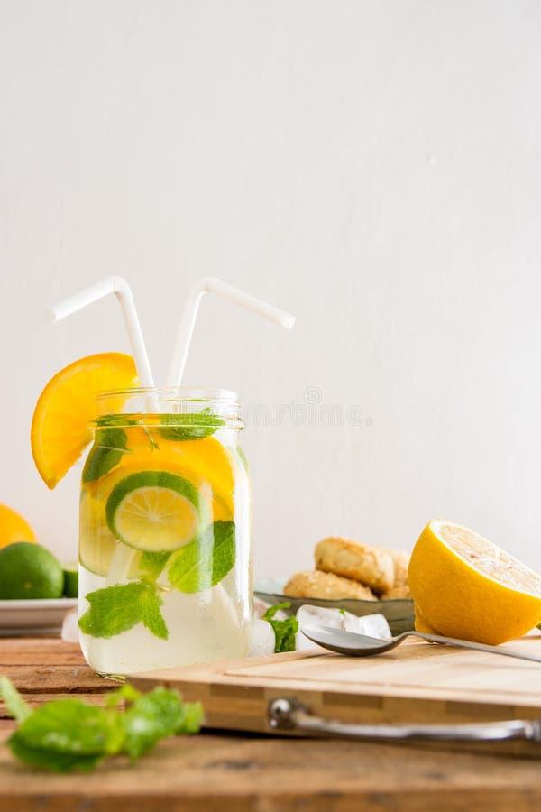El verano sabroso infundió la bebida de la naranja, de la menta, del limón y de la cal en la sobremesa con el espacio de la copia foto de archivo libre de regalías
