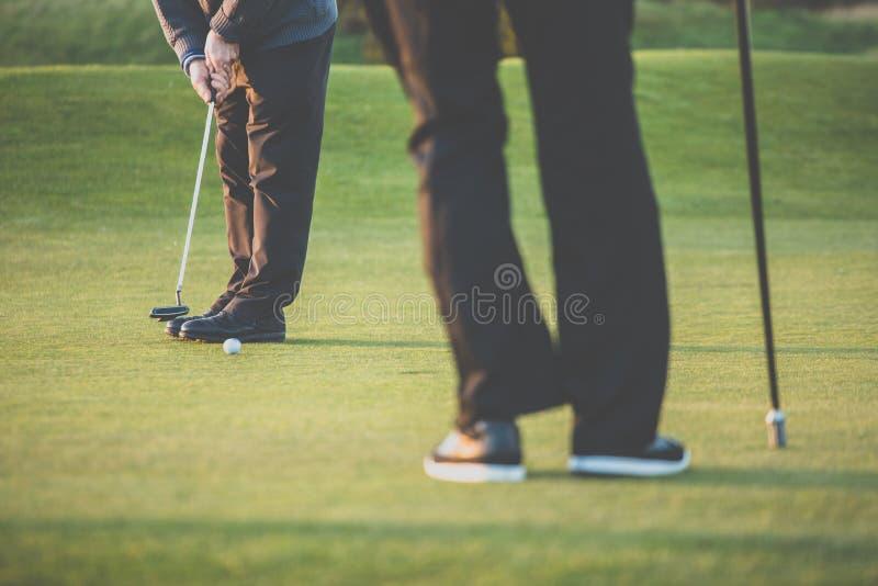 El verde del golf sceen - al golfista que pone cerca del agujero, putt corto foto de archivo libre de regalías