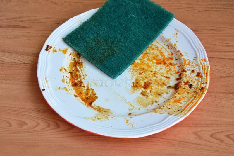 El verde friega la mancha de la comida del lavado de la esponja en el plato blanco fotos de archivo
